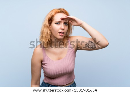 Young woman over isolated blue background looking far away with hand to look something