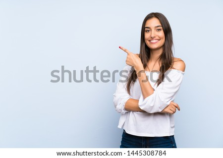 Young woman over isolated blue background pointing finger to the side