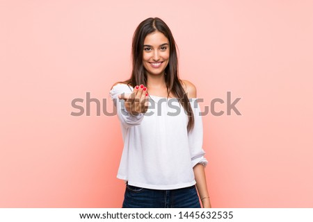 Young woman over isolated pink background inviting to come with hand. Happy that you came ストックフォト ©