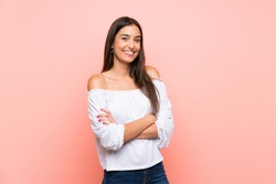 Young woman over isolated pink background keeping the arms crossed in frontal position