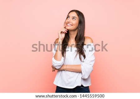 Young woman over isolated pink background thinking an idea while looking up
