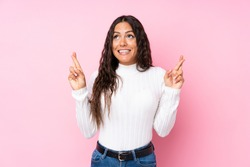 Young woman over isolated pink background with fingers crossing and wishing the best