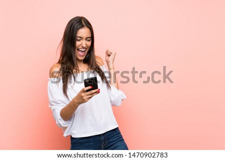 Young woman over isolated pink background with phone in victory position