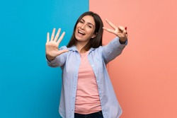 Young woman over pink and blue wall counting seven with fingers