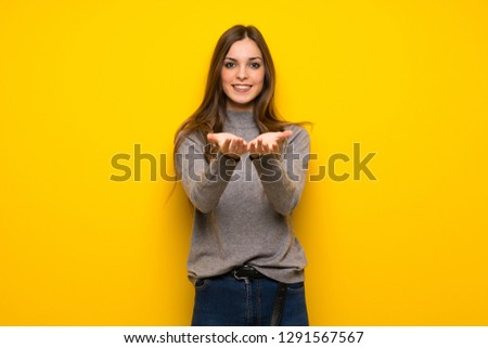Young woman over yellow wall holding copyspace imaginary on the palm to insert an ad #1291567567