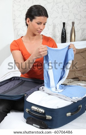 Young woman packing up her suitcase