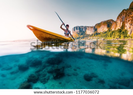 Young woman paddles kayak in a tropical sea. Splitted shot with underwater stones view