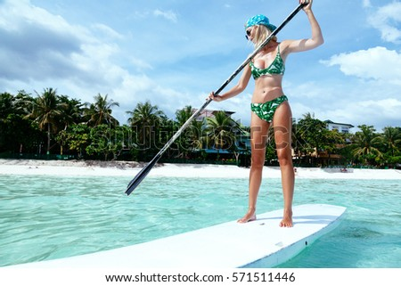 Young woman paddling on SUP board on the tropical beach. Active summer vacations with paddle board.