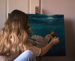 Young woman painting an underwater scene with oil on canvas.