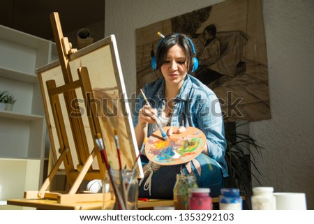Young woman painting and listens to music