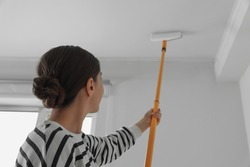 Young woman painting ceiling with white dye indoors, back view