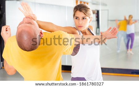 Young woman paired up with male partner in self defense training, practicing basic palm strike Stock fotó ©