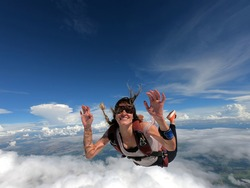 Young woman parachutist smiling in free fall. Perfect concept of happiness and freedom.
