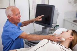 Young woman patient undergoing examination thyroid lying by elderly man doctor with ultrasonography device