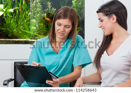 Young woman paying bill through credit card to female dentist in clinic