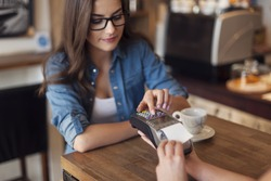Young woman paying for cafe by credit card reader