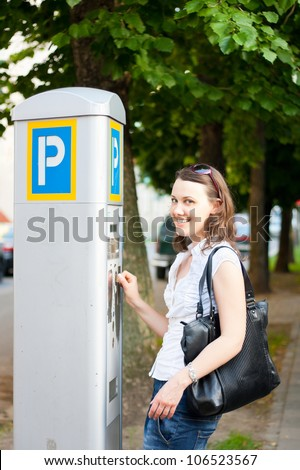 Young woman paying for parking in the street