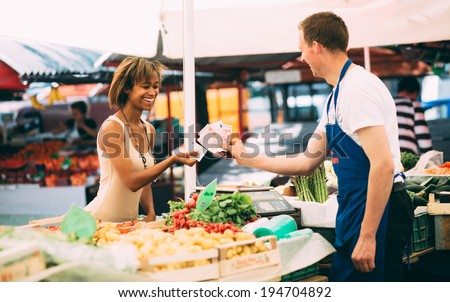 Young woman paying for produce at farmers market