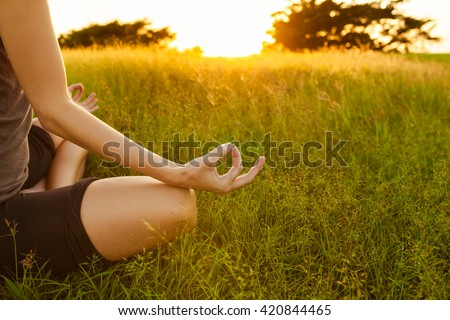 Young woman peacefully meditating in a open field. #420844465