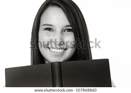young woman peering over a hard back book