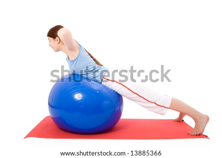Young woman performing fitness exercises with a fitness ball