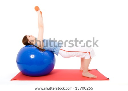 Young woman performing fitness exercises with a fitness ball and dumbbells