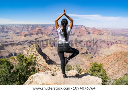 Young Woman Performing One-Legged Yoga Position on Rocky Ledge in front of the Grand Canyon - Grand Canyon National Park, Arizona, USA