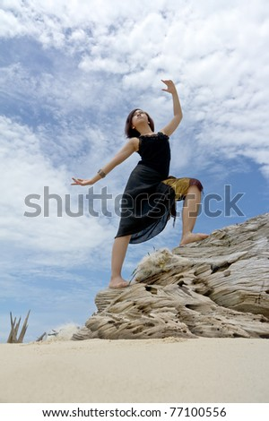 Young woman performs on beach of tropical island during holiday