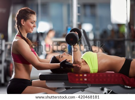 Young woman personal trainer helping with chest workout