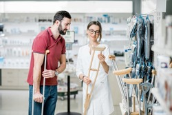 Young woman pharmacist helping to choose crutches for the man in the pharmacy supermarket