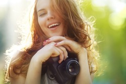 Young woman photographer. Soft colors, focus on mouth.