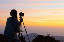 Young woman photographer taking picture of landscape when sunrise  at mountain peak.Travel and hobbies concept.