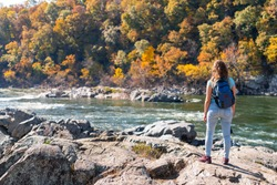 Young woman photographer with backpack and camera looking at view of Potomac river in Great Falls with autumn colorful foliage in Maryland