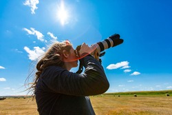 Young woman photographer with telephoto lens attached to DSLR camera shooting towards the sky i a bright sunny day. Copy space on top, lens flares