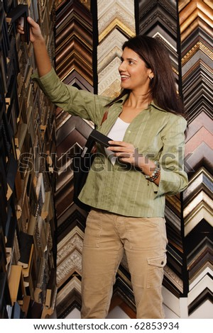 Young woman picking out picture frames