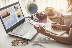 Young woman planning vacation trip and searching information or booking an hotel on a smart phone and laptop, Travel plan concept