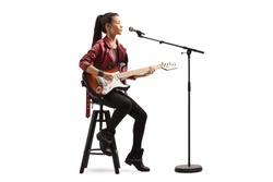 Young woman playing a guitar and singing on a microphone isolated on white background