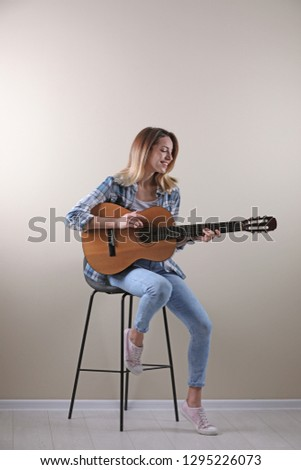 Young woman playing acoustic guitar near grey wall