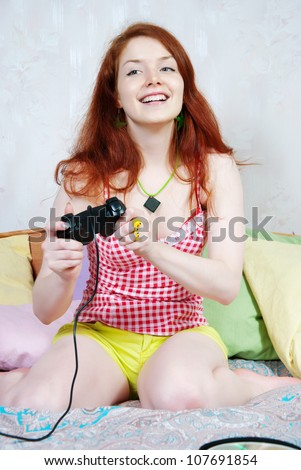 Young woman playing computer games on the bed at home