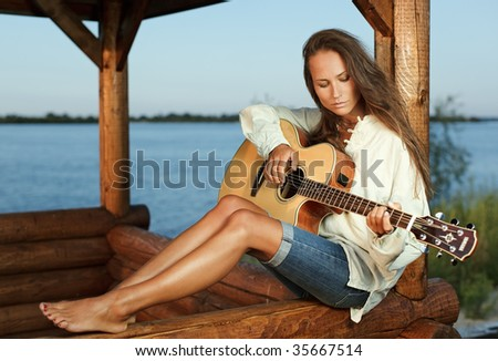 Young woman playing guitar in summerhouse on sunset