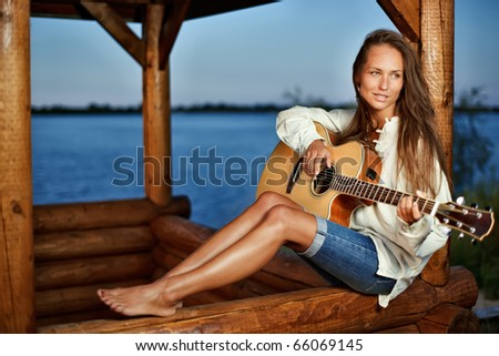 Young woman playing guitar in summerhouse on sunset - stock photo