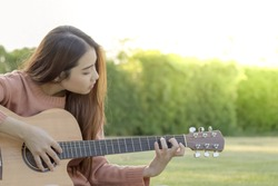 Young woman playing guitar on nature background.