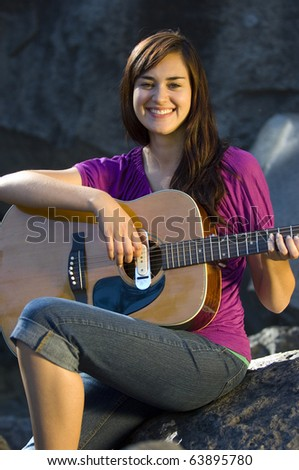 Young woman playing guitar on rocks in summer
