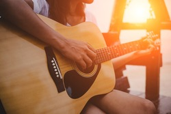Young woman playing guitar while sitting on the beach.