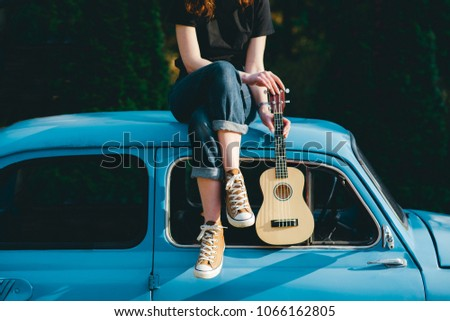 Young woman playing on ukulele near the blue little vintage car in the forest sunset