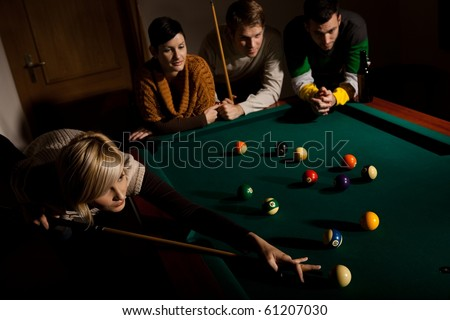 Young woman playing snooker, aiming at white ball with cue, other people watching.?