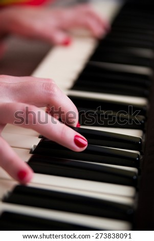 Young woman playing the piano. Music and education concept