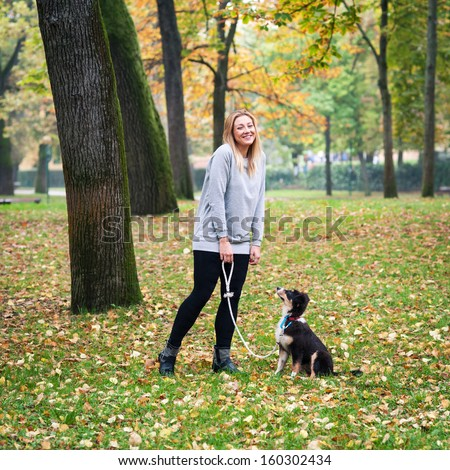 Young woman playing with Australian Shepherd dog outdoors in the park.