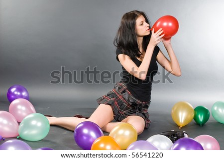 Young woman playing with baloons in studio at grey background