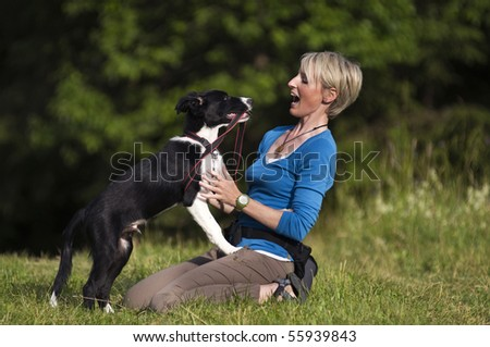 Young woman playing with border collie dog outdoor